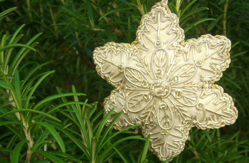 An ivory coloured, fabric Christmas star with gold beading hangs amid green foliage