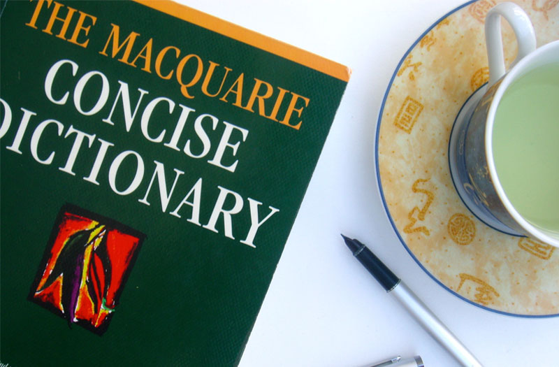 The Concises Macquarie Dictionary, artfully arranged with a pen and a cup of tea