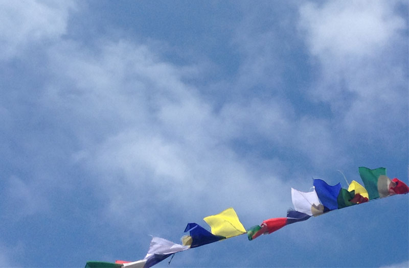 Buddhist prayer flags billowing in a blue sky