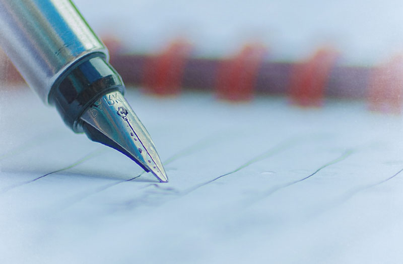 The inky nib of a silver fountain pen writing on paper