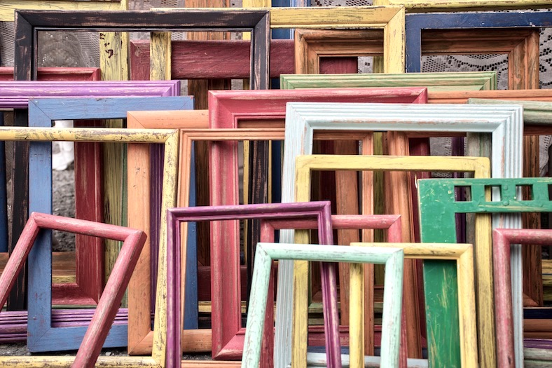 A collected of empty wooden picture frames, painted in a range of colours, leaning up against each other.