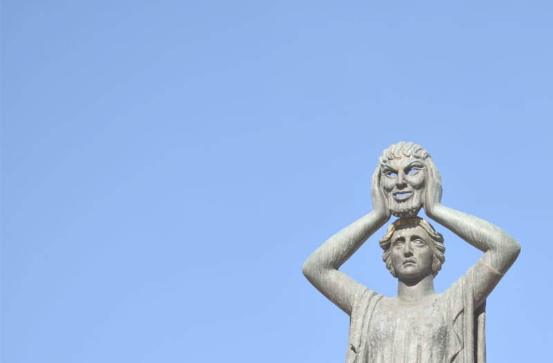 Image shows a statue of a person who is holding up a mask and revealing a true face
